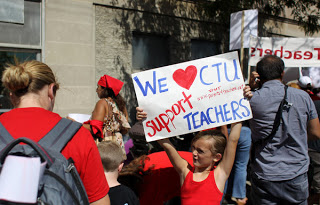 "Courtney Sinisi (cq), left, stands next to her daughter Mia, 7, while the second grader holds up a sign in support of the Chicago Teachers Union at the CTU ""strike headquarters"" outside Teamster City Local 705 in Chicago on Saturday, Sept. 8, 2012. Teachers, paraprofessionals, school clinicians, parents and supporters picked up picket signs and other strike materials. Members of the CTU plan to strike Monday if contract negotiations fail. (Keri Wiginton/Chicago Tribune) B582362464Z.1 ....OUTSIDE TRIBUNE CO.- NO MAGS, NO SALES, NO INTERNET, NO TV, CHICAGO OUT, NO DIGITAL MANIPULATION..."